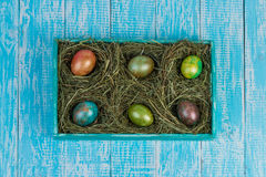 Easter eggs. Decorated eggs for Easter in the nests of hay on a decorated tray. In decorating a wooden background Stock Image