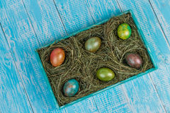 Easter eggs. Decorated eggs for Easter in the nests of hay on a decorated tray. In decorating a wooden background Stock Photo