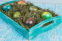 Easter eggs. Decorated eggs for Easter in the nests of hay on a decorated tray. In decorating a wooden background Stock Photos