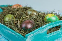 Easter eggs. Decorated eggs for Easter in the nests of hay on a decorated tray. In decorating a wooden background Stock Photography