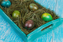 Easter eggs. Decorated eggs for Easter in the nests of hay on a decorated tray. In decorating a wooden background Royalty Free Stock Images
