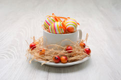Easter eggs decorated with straw and small wild apples Stock Photography