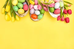 Easter eggs decoration colorful tulip flowers yellow background. Easter eggs decoration and colorful tulip flowers on yellow background stock image