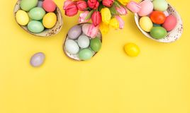 Easter eggs decoration pink tulip flowers yellow background. Easter eggs decoration with pink tulip flowers on yellow background royalty free stock image