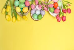 Easter eggs decoration tulip flowers yellow background. Easter eggs decoration with colorful tulip flowers on yellow background royalty free stock photos