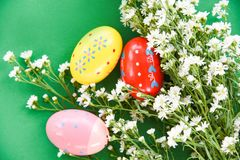 Easter eggs decoration white cutter flower on green background. Top view royalty free stock images