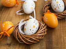 Easter eggs decorations with wicker nest and white feather, pain Royalty Free Stock Image