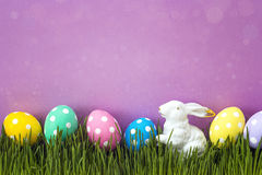 Easter eggs with a decorative hare in fresh green grass on purpl Royalty Free Stock Photography