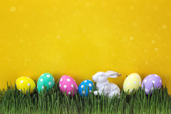 Easter eggs with a decorative hare in fresh green grass on yello Royalty Free Stock Image