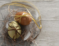 Easter eggs in a decorative nest with feathers on old wooden background Stock Photography