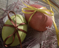 Easter eggs in a decorative nest with feathers on old wooden background Stock Images