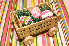 Easter eggs delivery. Easter eggs on a wooden toy chariot over colored background royalty free stock photos