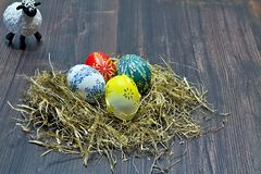 Easter eggs deposited in the hay on the wooden board. Colored Easter eggs deposited in the hay on the wooden board Royalty Free Stock Photos