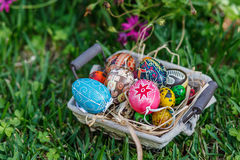 Easter eggs. Diverse Easter eggs in a basket, placed on a grass Stock Photos