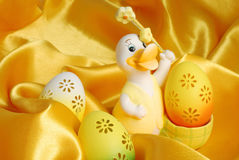 Easter eggs and duck. Easter eggs on golden sateen background stock photos
