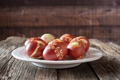Easter eggs dyed with onion peels with a pattern of fresh herbs on a plate.  royalty free stock photo
