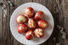 Easter eggs dyed with onion peels with a pattern of fresh herbs on a plate. Easter eggs dyed with onion peels with a pattern of fresh herbs on a vintage plate stock image