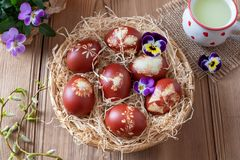 Easter eggs dyed with onion peels and a cup of whey. Easter eggs dyed with onion peels with a pattern of fresh herbs in a wicker basket, with a cup of fresh whey royalty free stock images
