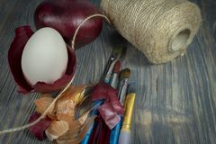 Easter eggs dyed with onion skins conceptual image. Fresh egg balancing in a dried onion skin, painting brushes, ball of brown twine and dried onion skin on a royalty free stock image