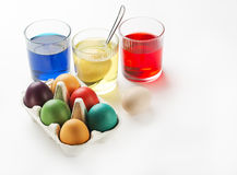 Eggs dyeing. Easter eggs dyeing in glass with colors Royalty Free Stock Photos