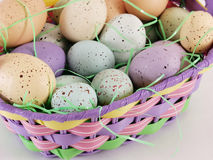 Easter Eggs in an Easter Basket. Multi colored pastel speckled eggs in an Easter basket with Easter grass Royalty Free Stock Photo
