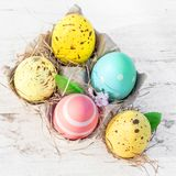 Easter eggs in egg cartoon box on white rustic wooden background. Close up. Festive decorations. Happy Easter Royalty Free Stock Photo