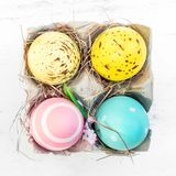 Easter eggs in egg cartoon box on white rustic wooden background. Close up. Festive decorations. Happy Easter Stock Photo