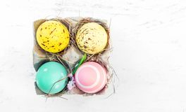 Easter eggs in egg cartoon box on white rustic wooden table with. Copy space. Festive decorations. Happy Easter Royalty Free Stock Photos