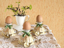 Easter eggs in eggcups with gold spoons. Next currant branches with leaves and flowers Royalty Free Stock Photos
