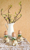 Easter eggs in eggcups with gold spoons. Next currant branches with leaves and flowers Royalty Free Stock Image