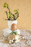 Easter eggs in eggcups with gold spoons. Next currant branches with leaves and flowers Stock Photos