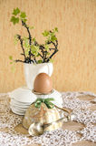 Easter eggs in eggcups with gold spoons. Next currant branches with leaves and flowers Blurred background Royalty Free Stock Photo