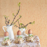 Easter eggs in eggcups with gold spoons. Next currant branches with leaves and flowers. Selective focus Stock Images
