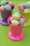 Easter eggs in eggcups. Small Easter eggs in pink eggcup on green background Royalty Free Stock Image
