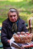 Easter painted colored eggs and an old woman in background - Bucharest, Romania Stock Photo