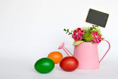 Easter eggs and fabric flowers arranged in watering bucket on light background Stock Photography