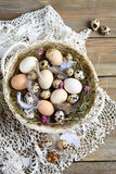Easter eggs and feathers in the basket Stock Photos