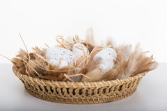 Easter eggs and feathers in brown basket. On table Royalty Free Stock Image