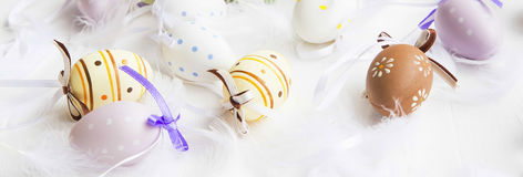 Easter eggs with feathers on white painted wooden background Stock Images