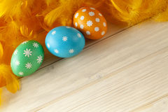 Easter eggs and feathers on wooden boards Stock Images