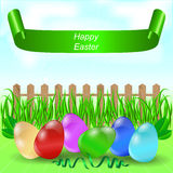 Easter eggs on the field with grass, a banner and a wooden fence. Royalty Free Stock Photos