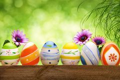 Easter eggs, flowers and bokeh background Royalty Free Stock Photo