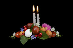 Easter eggs with flowers, chocolates and cakes on the background of burning candles Royalty Free Stock Image