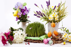 Easter eggs and flowers with grass on white background Stock Photo