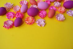 Easter eggs and flowers made of paper on a yellow background. The colors are pink, burgundy, fuchsia and yellow. Spring. Royalty Free Stock Images