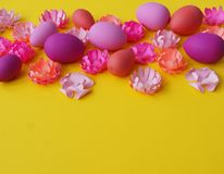 Easter eggs and flowers made of paper on a yellow background. The colors are pink, burgundy, fuchsia and yellow. Spring. Royalty Free Stock Image