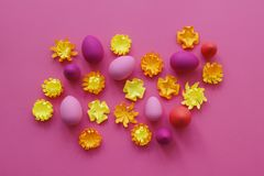 Easter eggs and flowers made of paper on a yellow background. The colors are pink, burgundy, fuchsia and yellow. Spring. Stock Photography