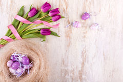 Easter eggs and flowers over white wooden table Royalty Free Stock Photos