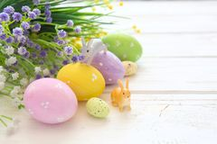 Easter eggs with flowers and small bunny toys on wooden board, easter holiday concept.  Stock Photo