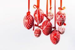 Easter eggs with folk Ukrainian pattern hang on red ribbons from right side on white background. Ukrainian traditional eggs. Pisanka and krashanka Royalty Free Stock Photo